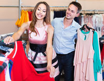 Young woman and man looking for new dress in showroom Royalty Free Stock Photos