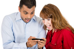 young woman and man looking shocked with opened mouth on a cell phone reading an sms, e-mail or viewing latest news Royalty Free Stock Photos