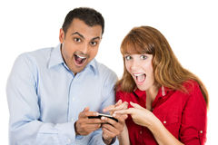 Young woman and man looking shocked with opened mouth on a cell phone reading an sms, e-mail or viewing latest news Stock Images