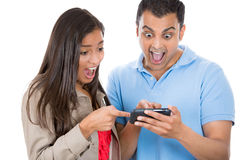 Young woman and man looking shocked with opened mouth on a cell phone reading an sms, e-mail or viewing latest news Royalty Free Stock Images