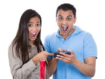 Young woman and man looking shocked with opened mouth on a cell phone reading an sms, e-mail or viewing latest news Stock Image