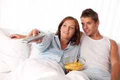 Young woman and man lying in bed. Watching television and eating crisps Stock Images