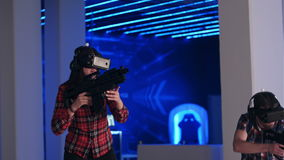 Young woman and man playing VR shooter game with virtual reality guns and vr glasses stock video footage