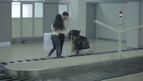 Young woman and man put their luggage to the trolley stock video footage