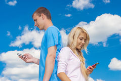 Young woman with man reading sms Stock Image