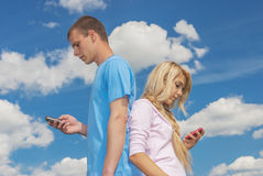 Young woman with man reading sms Royalty Free Stock Image
