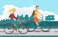 Young woman and man ride bike on highway. Healthy leisure. And freedom riding bike. Woman and man with backpacks pedaling on summer time. Highway and Forest in Stock Photo
