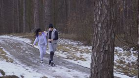 Young woman with man runs along slippery winter road in the forest. Young sport people makes morning exercises outdoors. Pretty woman and handsome man wearing stock footage