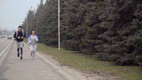 Young woman and man runs along urban road. Young sport people makes morning exercises outdoors. Pretty woman and handsome man wearing sportswear runs along the stock footage
