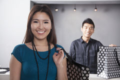 Young woman and man with shopping bags at fashion store, portrait Stock Images