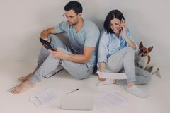 Young woman and man sit back to each other, do accounts together, make necessary calculations, surrounded with paper documents, royalty free stock photography