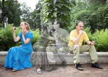 Young woman and the man sit on a bench in park separately, but in dreams they kiss Stock Images