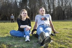 Young woman and man sitting on the lawn in the Park on the grass Royalty Free Stock Photo