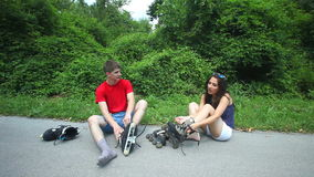 Young woman and man sitting on track, putting their rollerblades on their feet. stock video