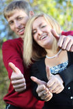 Young woman and man smile and thumb up in park royalty free stock photos