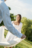 Young woman with man spreading picnic blanket in park. Young women with men spreading picnic blanket in park Royalty Free Stock Photos