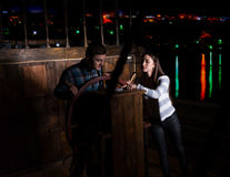 Young woman and man stand at the helm of the ship and look at th. Young women and men stand at the helm of the ship and look at the compass at dark night, escape stock image
