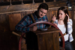 Young woman and man stand at the helm of the ship and look at th. Young women and men stand at the helm of the ship and look at the compass, escape the room game royalty free stock photography