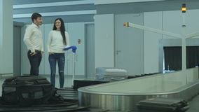 Young woman and man stay near the luggage conveyor and talk. The action takes place at the arriving hall of the airport near the baggage claim desk. Handsome man stock video footage