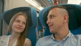 Young Couple is Talking and Laughing while Going by Train on Holiday Travel. Young Woman and Man are Talking and Laughing while Going by Train. Family Couple stock footage