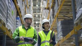 Young woman and man are talking and walking at warehouse during working day.