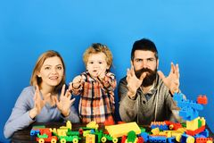 Young woman and man with toddler son playing with blocks. Young woman and man with toddler son playing with colorful plastic blocks on blue background royalty free stock photo