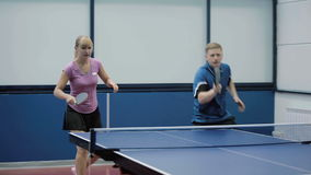 Young woman and man together playing in a table tennis. Shooting in front of the people. Young woman and man together playing a table tennis. The couple quickly stock video footage