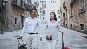 Young woman and man travelling together in springtime, walking with baggage through city