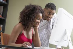 Young Woman With Man Using Computer Stock Photo