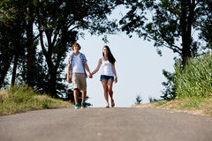 Young woman and man is walking on a road in summer outdoor Royalty Free Stock Photos