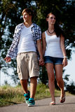 Young woman and man is walking on a road in summer outdoor Stock Photos