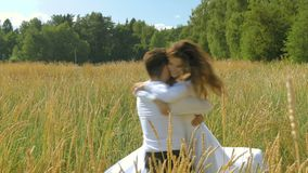 A young woman and a man in white suits flee to meet each other and embrace. On a sunny day, in a field with wheat. stock video