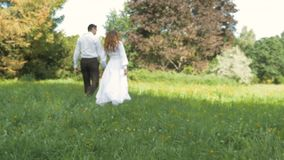 A young woman and a man in white suits are walking in the park. Hold hands, in the blur zone. Romantic date stock video footage