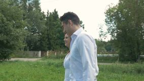A young woman and a man in white suits are walking in the park. Hold hands, in the blur zone. A young woman and a man in white suits are walking in the park stock video