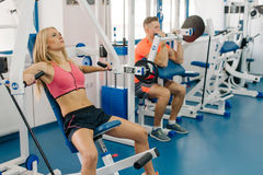 Young woman and man working out in gym. Couple making exercises for arms. Perfect bodies. Royalty Free Stock Images