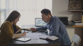 Young woman and a man working at studio loft. In the picture are the man and woman who are actively discussing the idea or approves the project. On the table lay stock footage