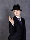 Young woman in manly style with mini cigar on gray background, girl in man`s suit and tie, white shirt and hat Stock Image