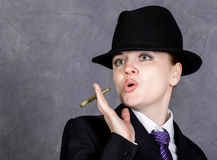 Young woman in manly style with mini cigar on gray background, girl in man`s suit and tie, white shirt and hat Stock Photos