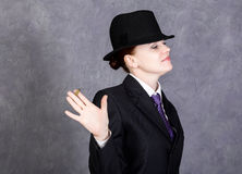 Young woman in manly style with mini cigar on gray background, girl in man`s suit and tie, white shirt and hat Stock Photo