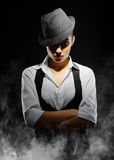 Young woman in manly style. On smoke background Stock Photo