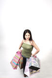 Young woman with many bags. A young woman poses with her hands on her hips while clutching several shopping bags Stock Images
