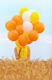 Young woman with many balloons on summer wheat field Royalty Free Stock Photos