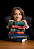 Young woman with many book at the desk Royalty Free Stock Images
