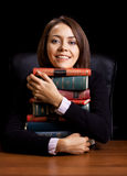 Young woman with many books at the desk Stock Image