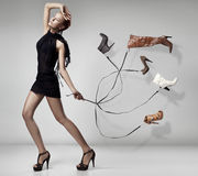 Young woman with many shoes.  Royalty Free Stock Photography