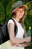 Young woman with map. Beautiful young woman standing in forest with backpack, map and bottle of water, smiling and looking in camera Royalty Free Stock Photos