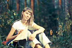 Young woman with map. Beautiful young woman sitting on  forest floor with backpack and map, smiling and looking away from camera Stock Images