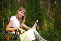 Young woman with map. Beautiful young woman sitting on  forest floor with backpack, map and bottle of water, smiling and looking in camera Stock Photography