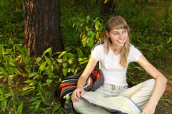 Young woman with map. Beautiful young woman sitting on  forest floor with backpack and map, smiling and looking away from camera Stock Photos