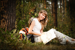 Young woman with map. Beautiful young woman sitting under tree in forest with backpack and map, smiling and looking in camera Royalty Free Stock Photography